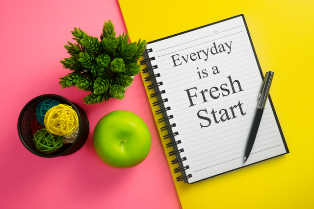 Everyday is a fresh start. Inspirational quote on notebook with pen, green apple and potted plant. afvallen met coach nutrition